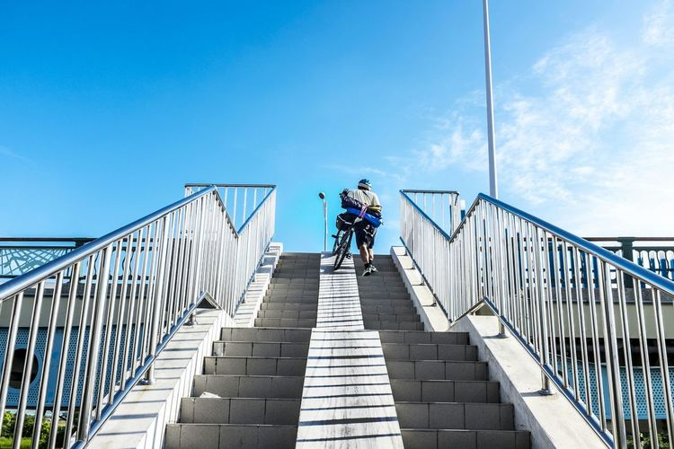 Rear View Of Cyclist Moving Up Staircase With Bicycle