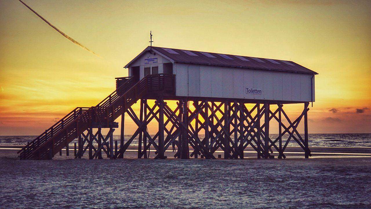 Stilt House At Beach During Sunset