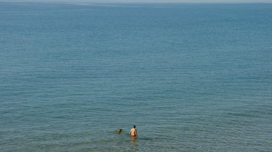 People standing on sea against sky