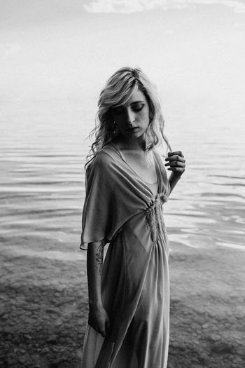 Beautiful Woman Beauty Black And White Fashion Hair Hairstyle Leisure Activity Lifestyles Long Hair Monochrome One Person Outdoors Portrait Real People Sea Standing Three Quarter Length Water Women Young Adult Young Women