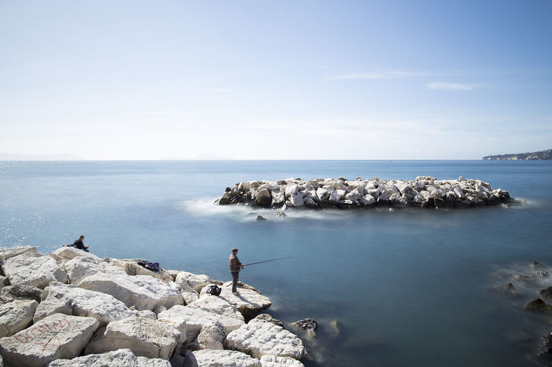 Side view of man standing on rock fishing in sea against sky