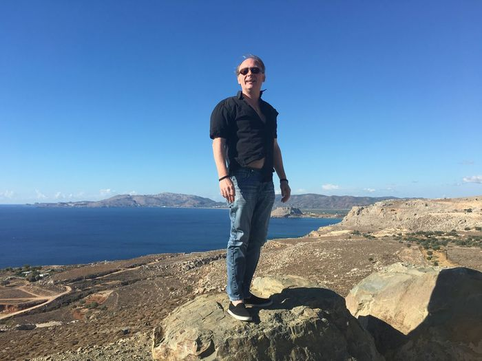 Mature Man Standing On Rock Formation Against Clear Blue Sky During Sunny Day