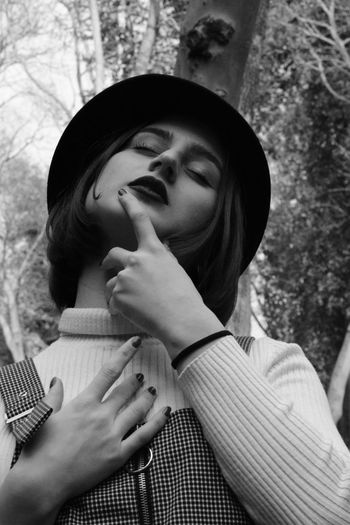 Low Angle View Of Young Woman Wearing Hat Against Trees
