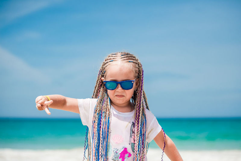 Girl wearing sunglasses while gesturing at beach against sky