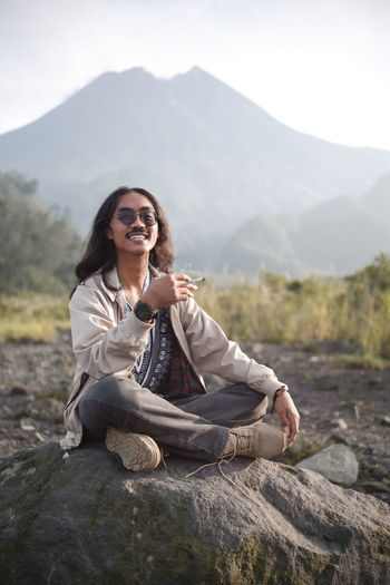 Relax and enjoy a cigarette on a rock with a view of mount merapi