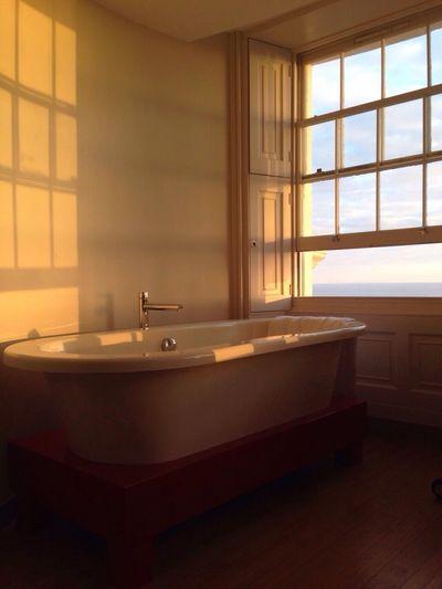 Free standing bathtub by window in bathroom