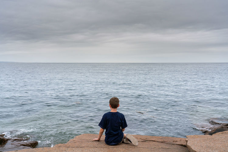 sitting by the waters edge Beauty In Nature Blue Boys Casual Clothing Child Cloud - Sky Horizon Horizon Over Water Leisure Activity Lifestyles Looking At View Men Nature One Person Real People Rear View Scenics - Nature Sea Sitting Sky Water