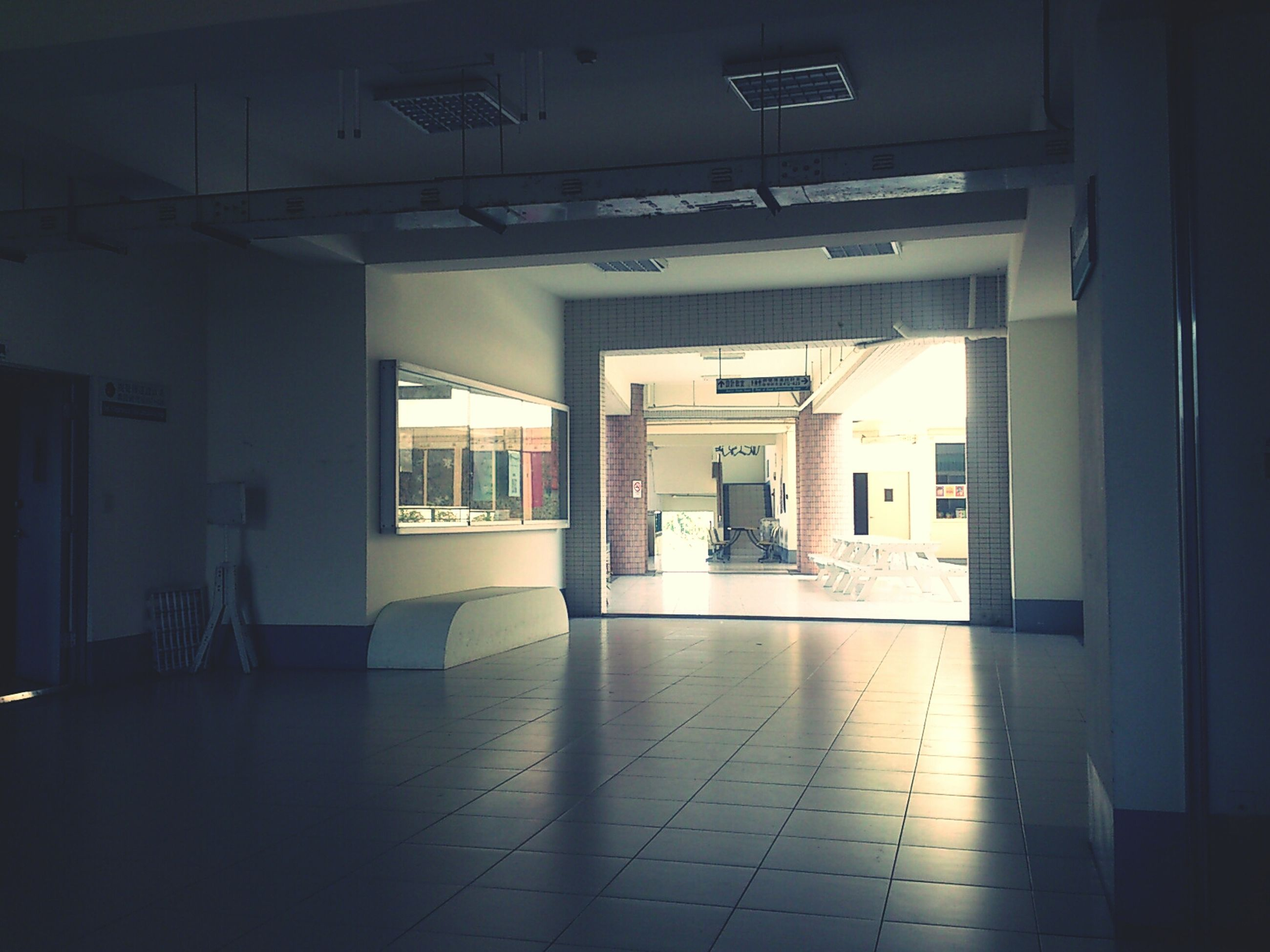 indoors, ceiling, architecture, empty, built structure, corridor, flooring, absence, interior, illuminated, window, tiled floor, door, lighting equipment, chair, no people, building, the way forward, reflection, modern