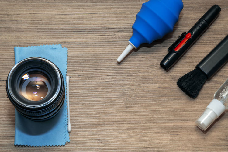 High angle view of camera lens and cleaning equipment on table