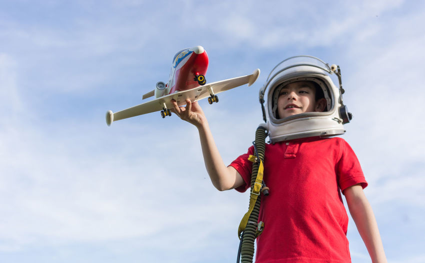 Low angle view of boy wearing astronaut helmet while flying model airplane against sky