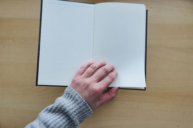 Midsection of person holding book on table