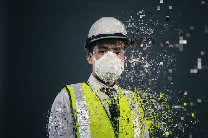Confident expression of young supervisor or engineer wearing white helmet and face mask dispersing into pixels effect Helmet Safety Protection Headwear Security Occupation Protective Workwear Portrait One Person Front View Protective Eyewear Hardhat  Headshot Men Adult Industry Standing Working Mature Men