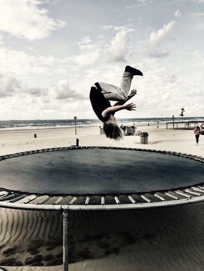 Boy jumping on trampoline at beach against sky