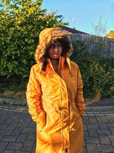 Portrait of woman wearing yellow jacket on footpath