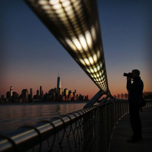 Man Photographing Cityscape Against Clear Sky During Sunset
