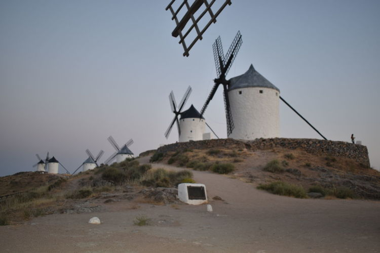 Traditional windmill on land against sky