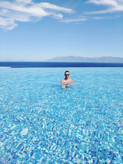 Mid distance view of man swimming in infinity pool against sky