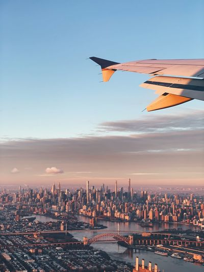 Cropped image of airplane flying over cityscape against sky