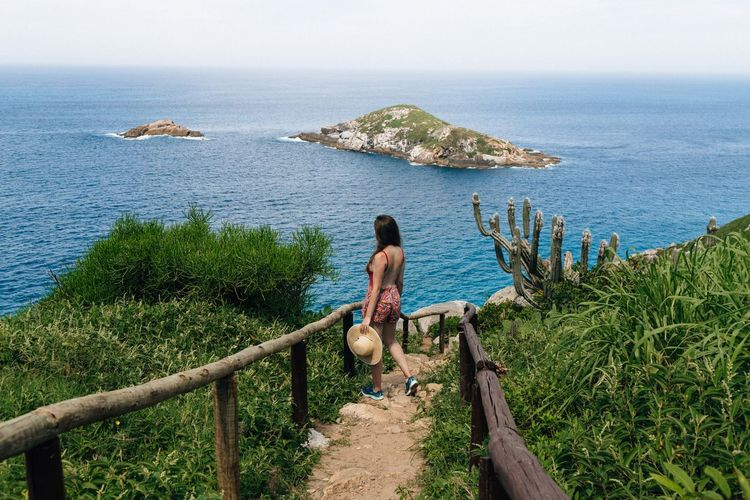 Woman walking against sea