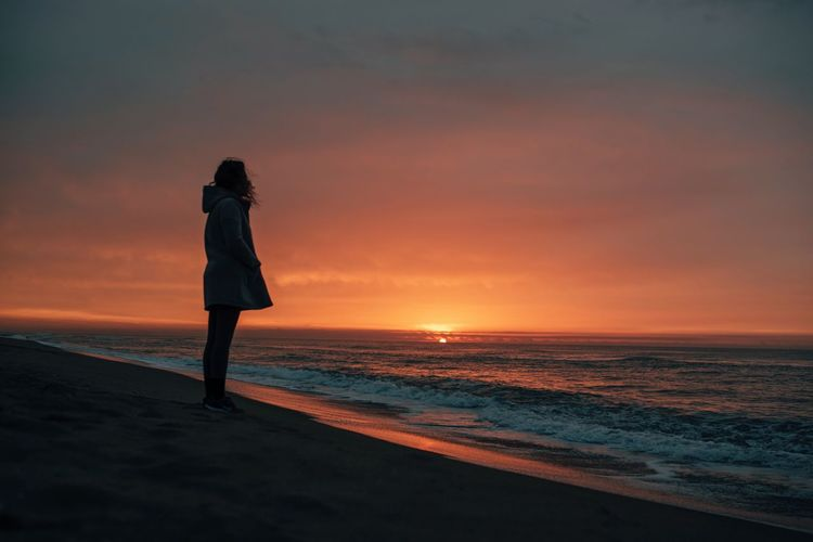 Woman standing on beach during sunset
