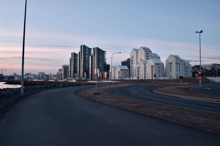 Road by buildings against sky in city at dusk
