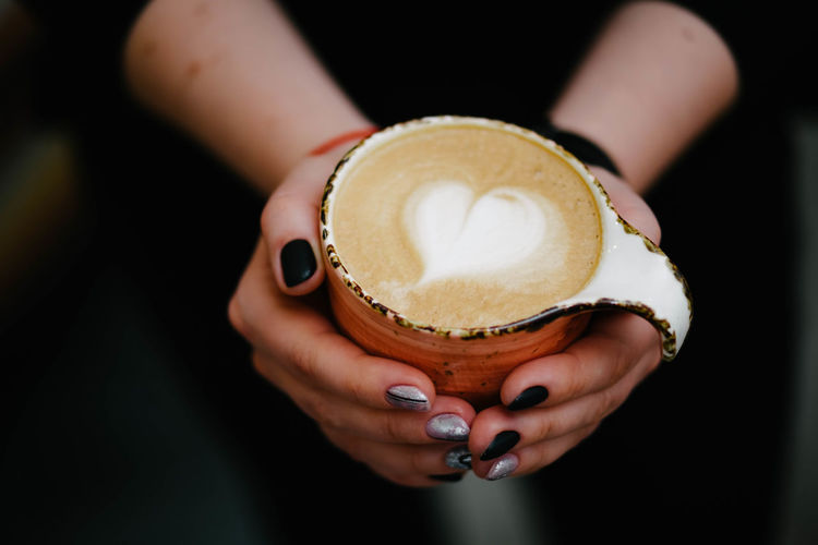 Close-up of woman holding coffee cup
