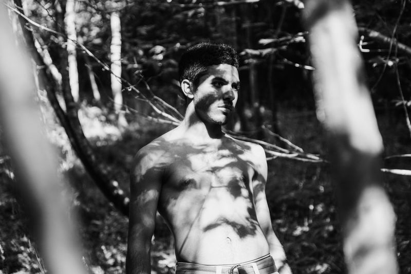 Portrait of young man standing in forest