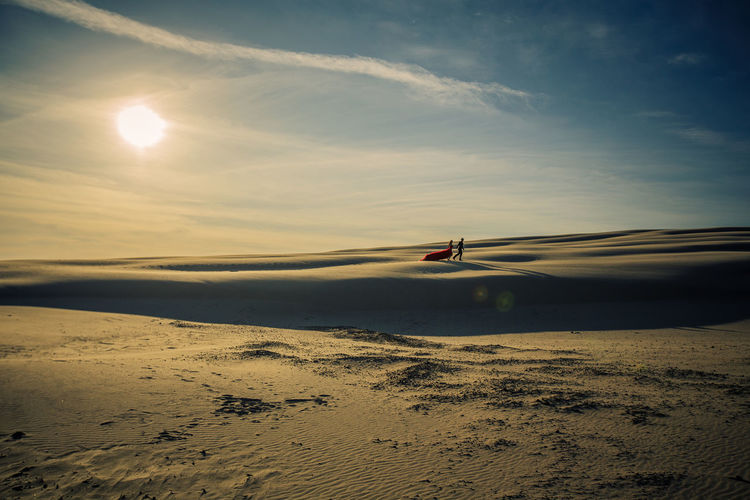 Couple on desert against sky during sunset