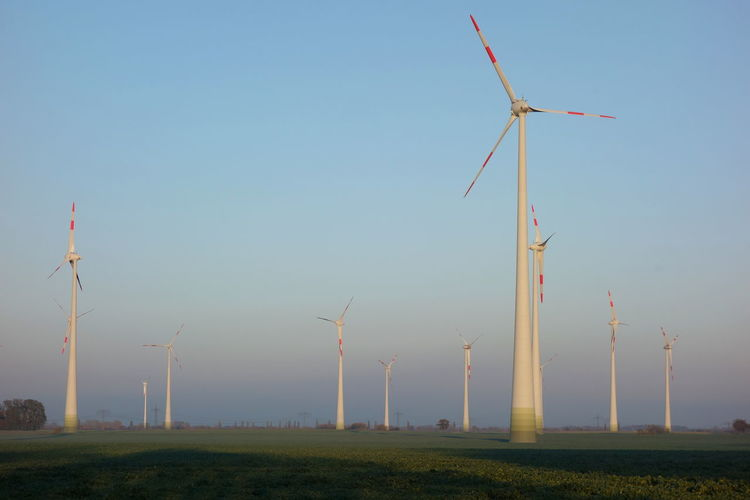 Low angle view of windmills on field against clear sky
