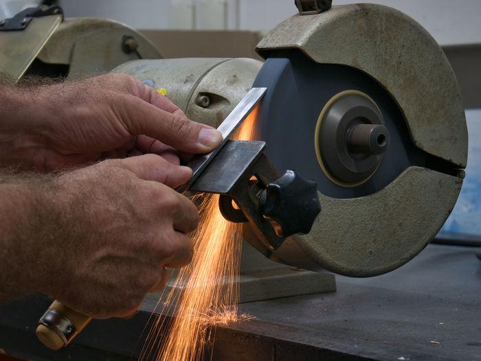 Cropped hands of man sharpening work tool on grinder