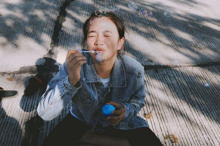 High angle view of beautiful woman blowing bubbles while sitting outdoors