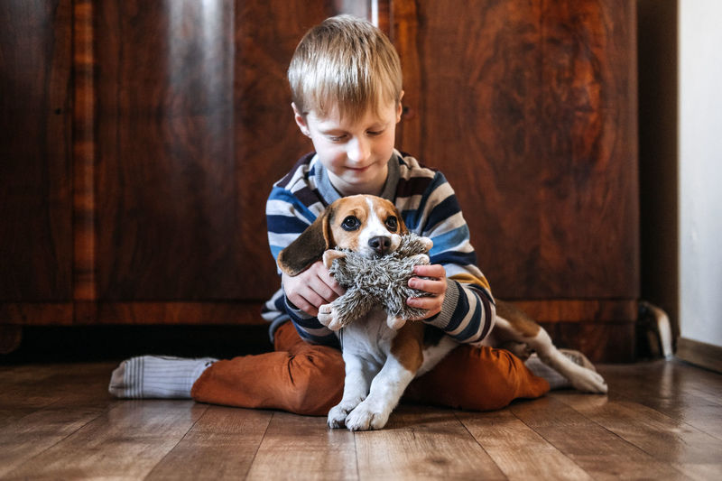 Boy with dog sitting on wooden floor