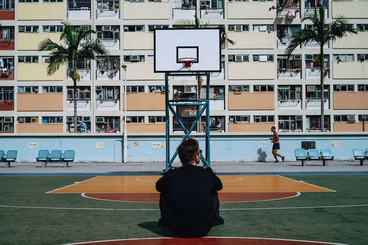 Rear view of man sitting on basketball court