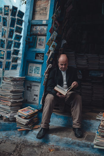 Full length of man sitting on book in building