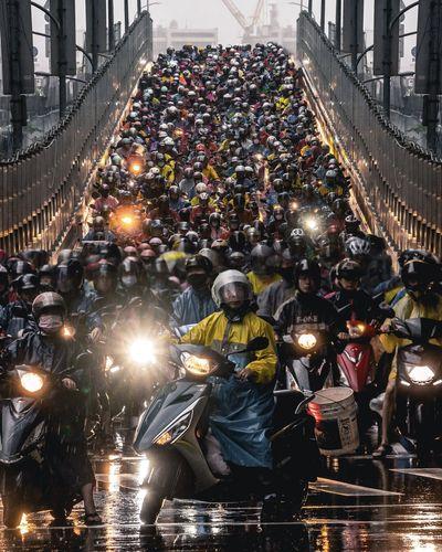 People on illuminated bridge in city at night