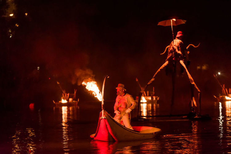 People by illuminated fire in water at night