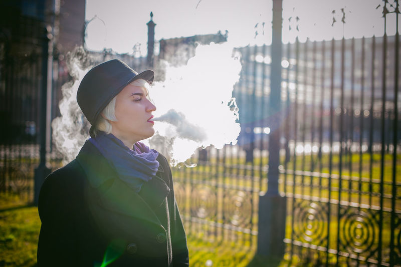 Young Woman Smoking While Standing At Park