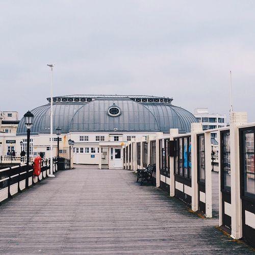 Eastbourne pier leading towards building against sky