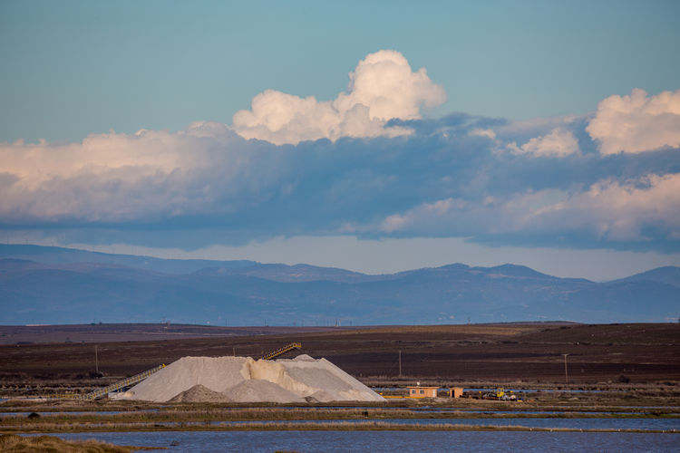 Scenic view of land and mountains against sky. salt pan's near porto lagos