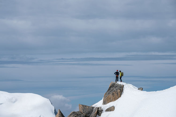 Friends standing on snowcapped mountain against sky