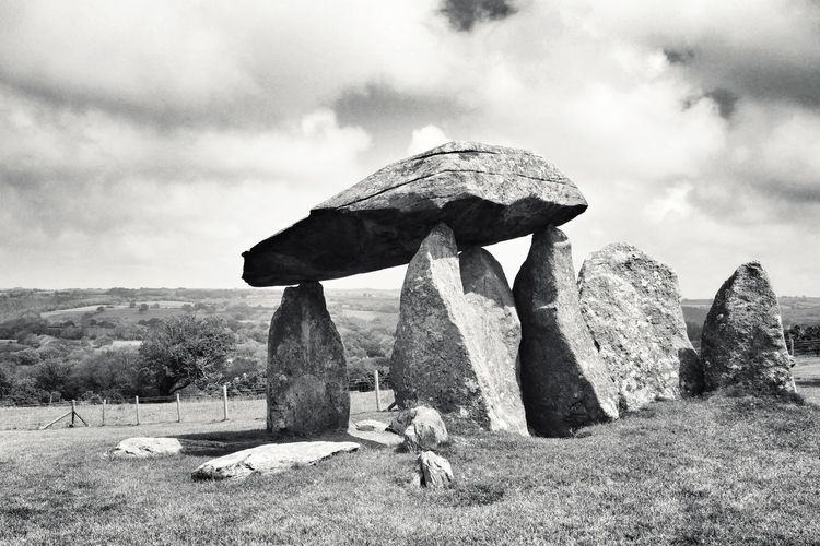 View of rock formation on field against sky