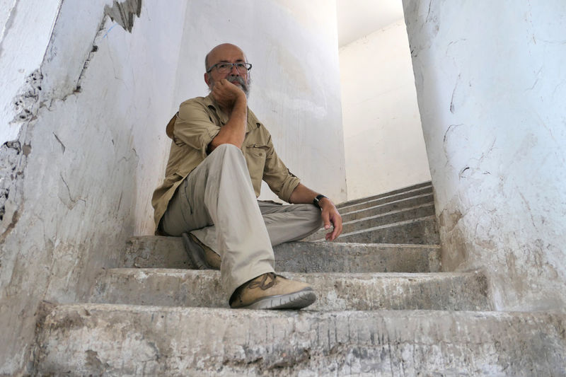 Full length of man sitting on staircase against wall