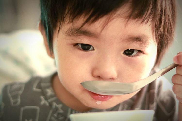 Close-up of boy drinking milk from spoon at home
