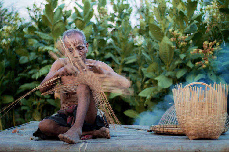 Shirtless Senior Man Making Wicker Basket While Sitting At Farm
