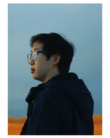 Portrait of man looking away against blue sky