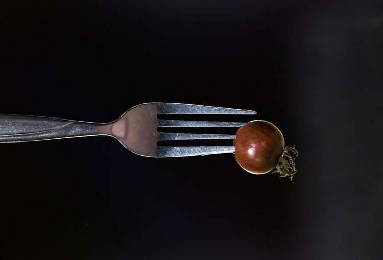 Small kumato tomato on fork isolated on the black background. Black Background Close-up Day Decor Food Food And Drink Fork Freshness Healthy Eating Indoors  Kitchen Utensil Kitchen Utensils Kumato Tomato No People Photo For Kitchen Interior Restaurant Decor Restaurant Interior Design Still Life Studio Shot Tomato Vegetable