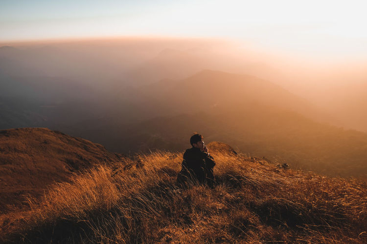 Man sitting on cliff against sky during sunset