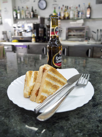 sandwich with sobrasada and a cold bottle of Estrella Galicia beer on counter of spanish bar Beer Bocadillo Breakfast Sandwich Tapas Almuerzo Bar Bottle Close-up Countertop Focus On Foreground Food Food And Drink Fork Freshness Indoors  Indulgence No People Plate Ready-to-eat Serving Size SLICE Sobrasada Tercio