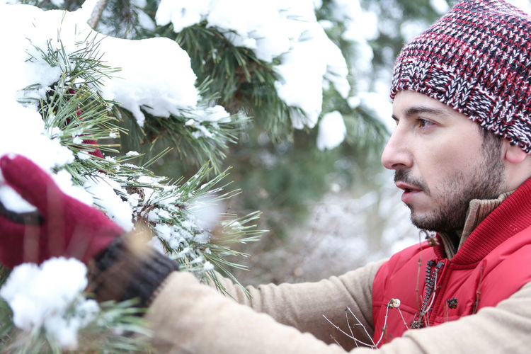 Side view of man looking at snow on coniferous tree during winter
