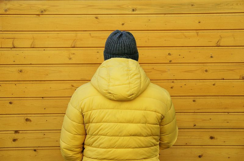 Rear View Of Man Wearing Yellow Coat